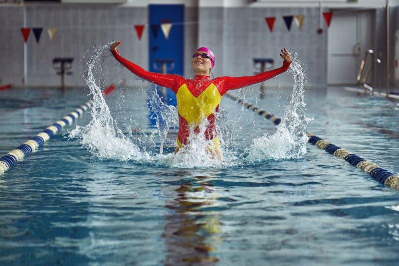 Den kvinnliga idrottsman nen i enguling baddräkt gör ett hopp för glädje i pölen royaltyfria bilder