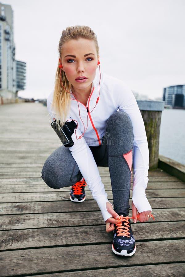 Den kvinnliga idrottsman nen som binder henne, snör åt för en körning royaltyfri fotografi