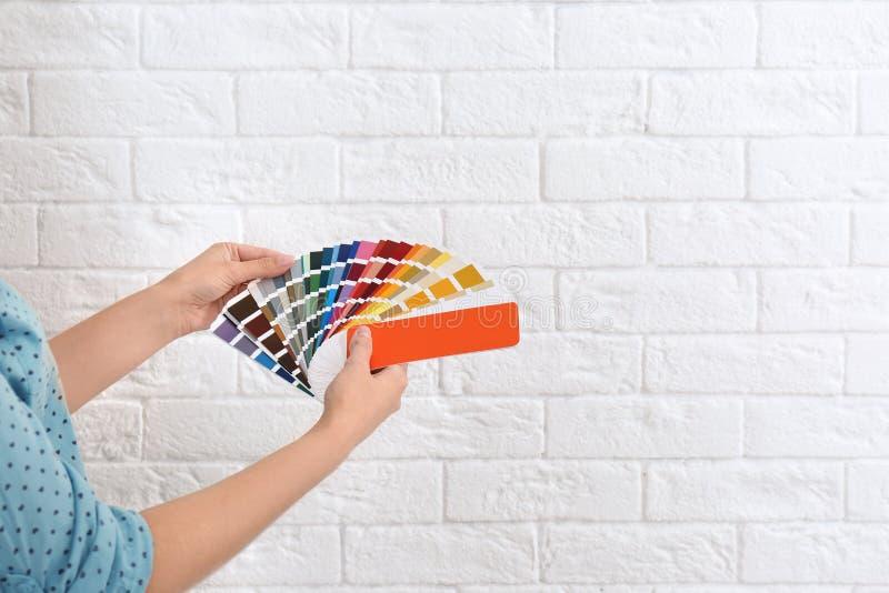 Den kvinnliga inreformgivaren med färgpaletten tar prov nära tegelstenväggen, closeup royaltyfria bilder