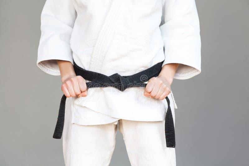Den kvinnliga kämpetorson poserar i den vita kimonot och sportive starkt a royaltyfria foton