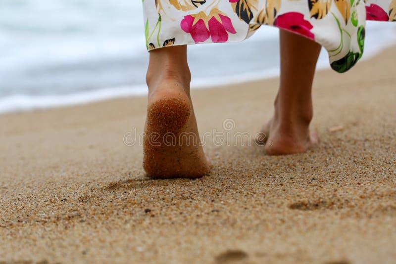 Den kvinnliga kala foten som går på stranden, sandpapprar closeupen arkivfoton
