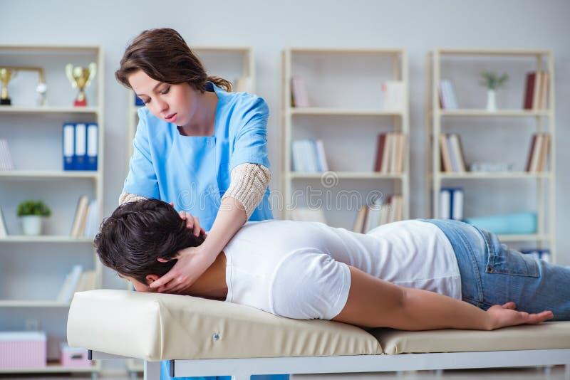 Den kvinnliga kiropraktordoktorn som masserar den manliga patienten arkivfoton