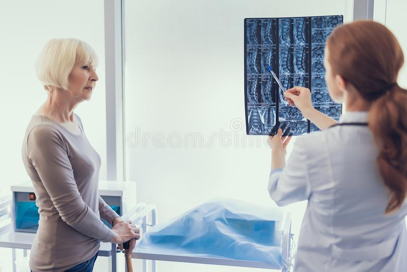 Den kvinnliga kirurgen analyserar röntgenfotografering i sjukhuset royaltyfri bild