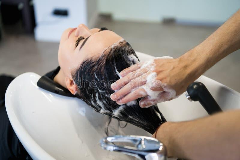 Den kvinnliga klienten som får hår, tvättade sig vid frisören i mottagningsrum arkivbilder