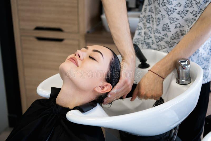 Den kvinnliga klienten som får hår, tvättade sig vid frisören i mottagningsrum royaltyfri fotografi