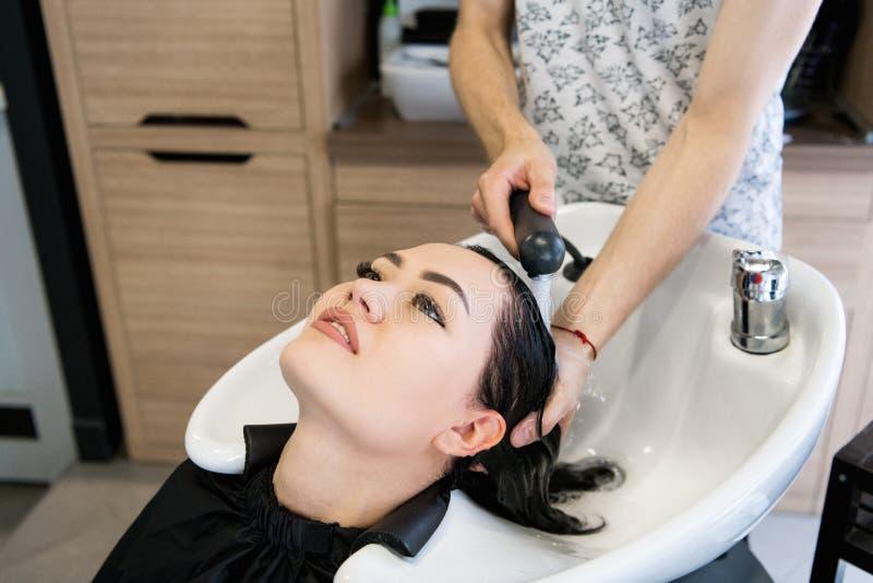 Den kvinnliga klienten som får hår, tvättade sig vid frisören i mottagningsrum royaltyfria foton