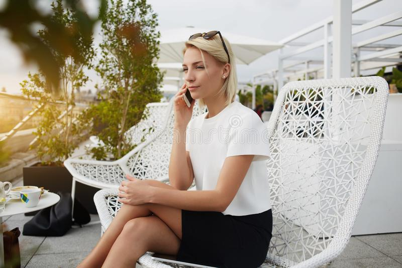 Den kvinnliga kompetenta advokaten kallar via celltelefonen, medan sitter i kafé arkivfoto