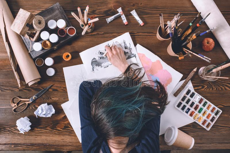 Den kvinnliga konstnären som sover på, skissar på arbetsplatsen arkivfoto