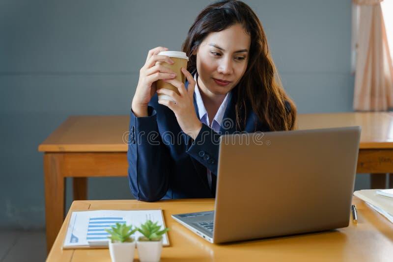 Den kvinnliga kontorsarbetaren bär mörkt - den blåa affärsdräkten arbetar med bärbara datorn, medan dricka kaffe, i att le framsi arkivfoto