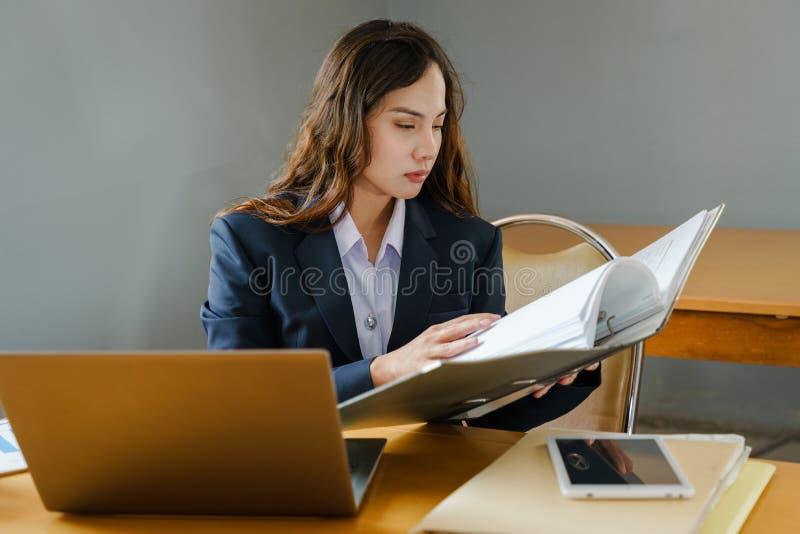 Den kvinnliga kontorsarbetaren bär mörkt - den blåa affärsdräkten som arbetar med dokumentmappen och högen av arbetspapper i allv arkivfoto