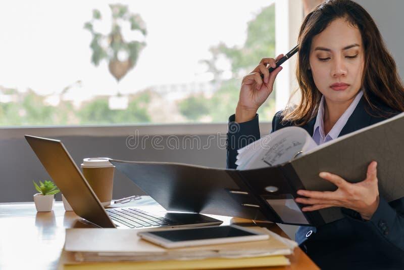 Den kvinnliga kontorsarbetaren bär mörkt - den blåa affärsdräkten som arbetar med dokumentmappen och högen av arbetspapper i allv arkivfoton