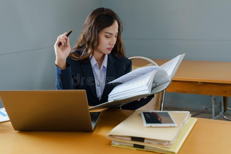 Den kvinnliga kontorsarbetaren bär mörkt - den blåa affärsdräkten som arbetar med dokumentmappen och högen av arbetspapper i allv royaltyfria foton