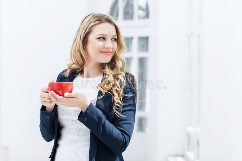 Den kvinnliga kontorsarbetaren som har kaffeavbrottet royaltyfri fotografi