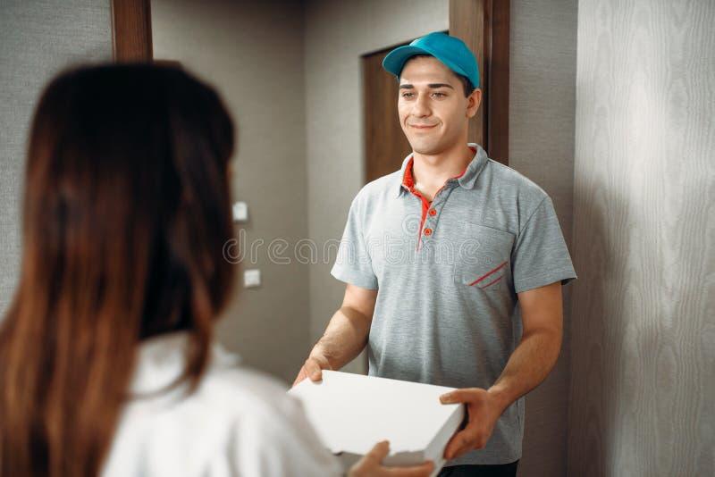 Den kvinnliga kunden undertecknar beställning till pizzaleveranspojken arkivbild