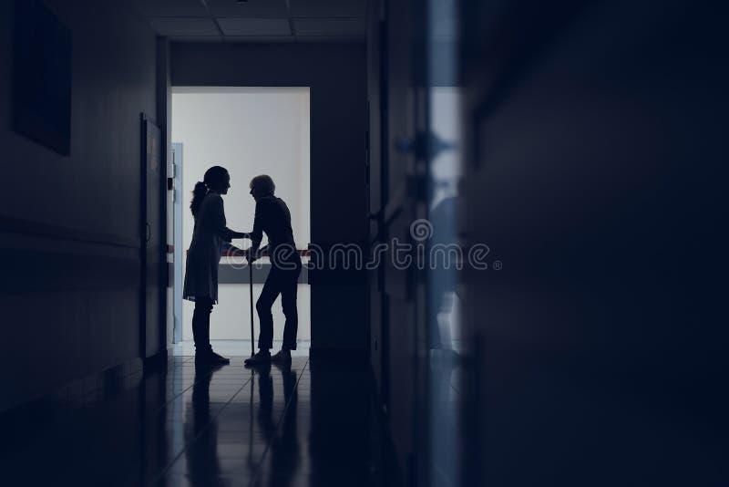 Den kvinnliga läkaren hjälper damen med rottingen i hall royaltyfria bilder