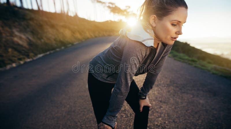 Den kvinnliga löparen som tar ett avbrott under hennes morgon, joggar anseende på en gata med solen i bakgrunden Kvinnaidrottsman royaltyfri foto