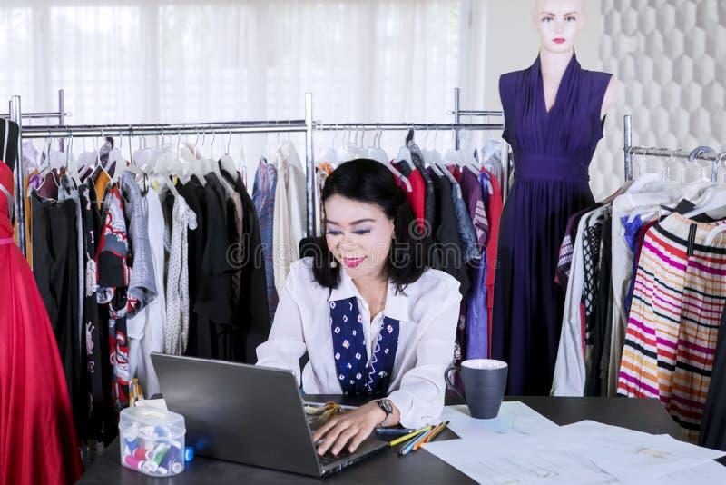 Den kvinnliga modeformgivaren arbetar med en bärbar dator royaltyfri foto