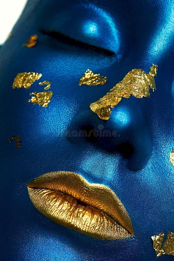 Den kvinnliga modellen med blått flår och guld- kanter för halloween för svart hår le för lång look pumpa för makeup sexigt skjut arkivfoton