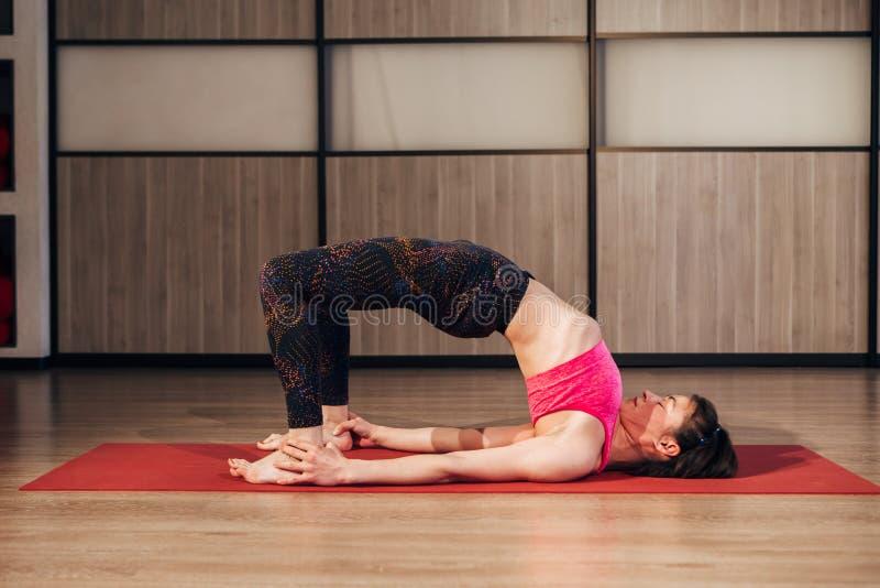Den kvinnliga modellen som gör yogabron, poserar på idrottshallen, den uppåtriktade pilbågen eller hjulställing fotografering för bildbyråer