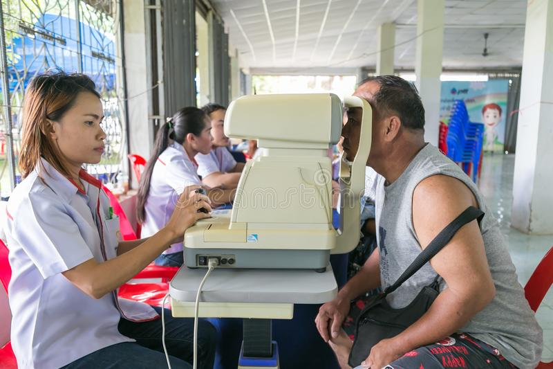Den kvinnliga Optictianen som undersöker det vuxna ögat för man` s i gemenskapservice arkivbild