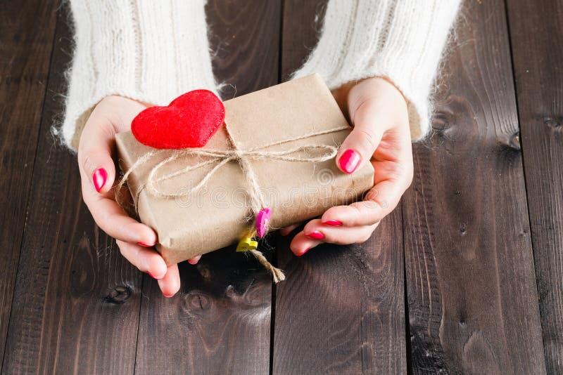 Den kvinnliga packen och ger gåva slåget in hantverkpapper fotografering för bildbyråer