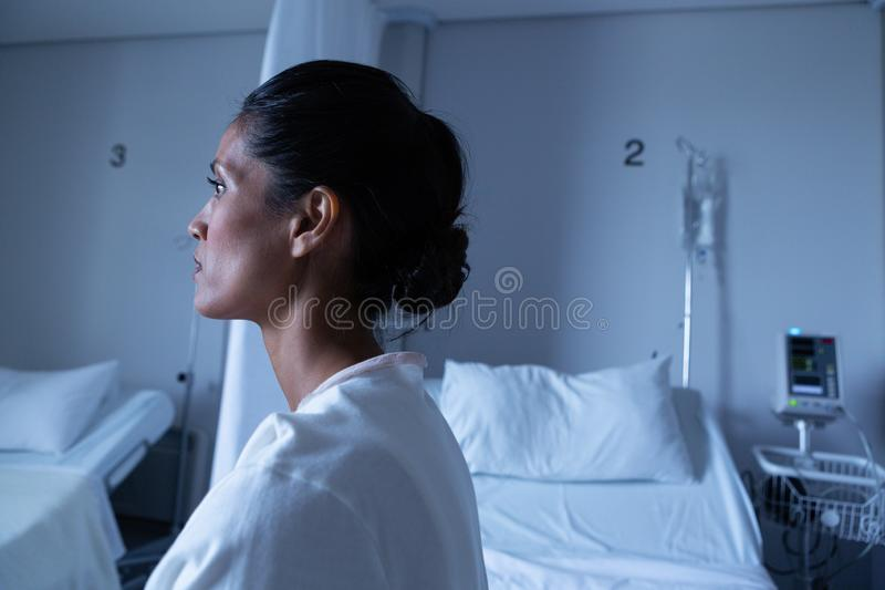 Den kvinnliga patienten som bort ser, medan sitta på säng, avvärjer in royaltyfria foton