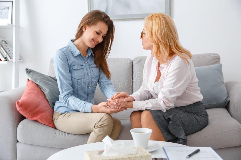 Den kvinnliga psychologystterapiperioden med klienten som sitter inomhus att rymma, räcker lyckligt royaltyfri foto
