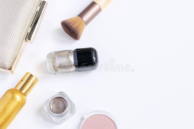 Den kvinnliga skönhettillbehören lägger framlänges - doft, den guld- kopplingpåsen, rodnaden, makeupborsten, ögonskuggor, vit bak arkivbild