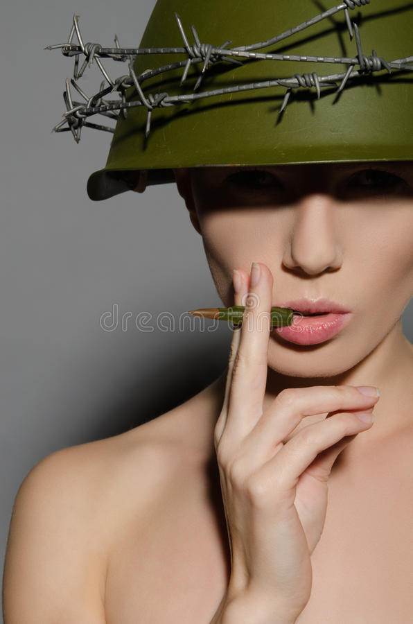 Den kvinnliga soldaten i hjälm röker en kula fotografering för bildbyråer
