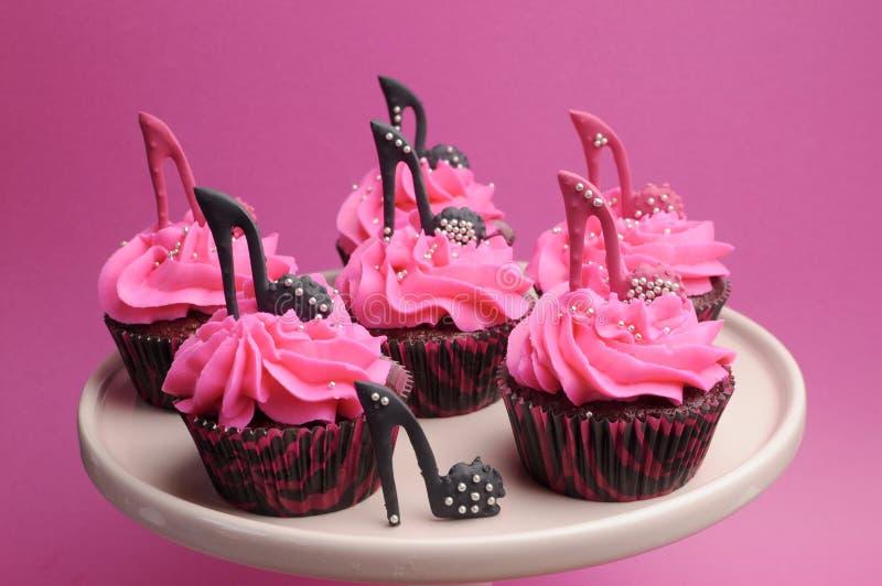 Den kvinnliga stiletten för den höga hälet skor dekorerade röda sammetmuffin för rosa färger och för svart royaltyfria foton
