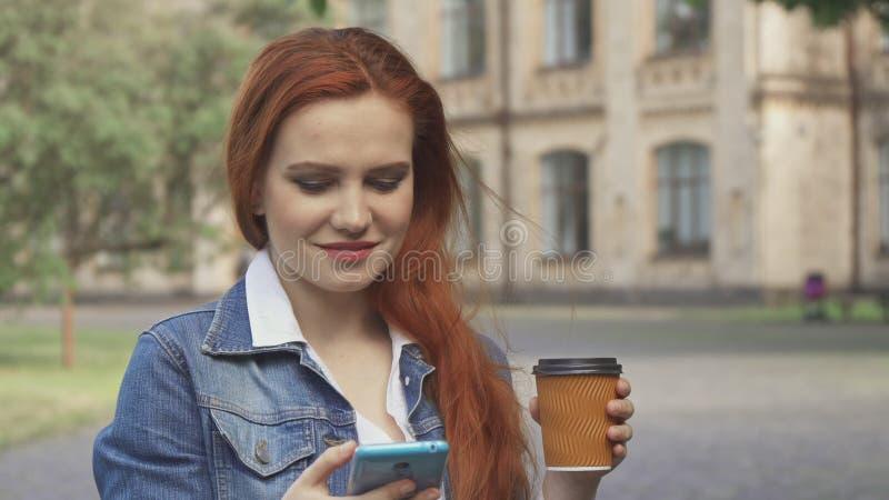 Den kvinnliga studenten dricker kaffe på universitetsområde royaltyfri foto