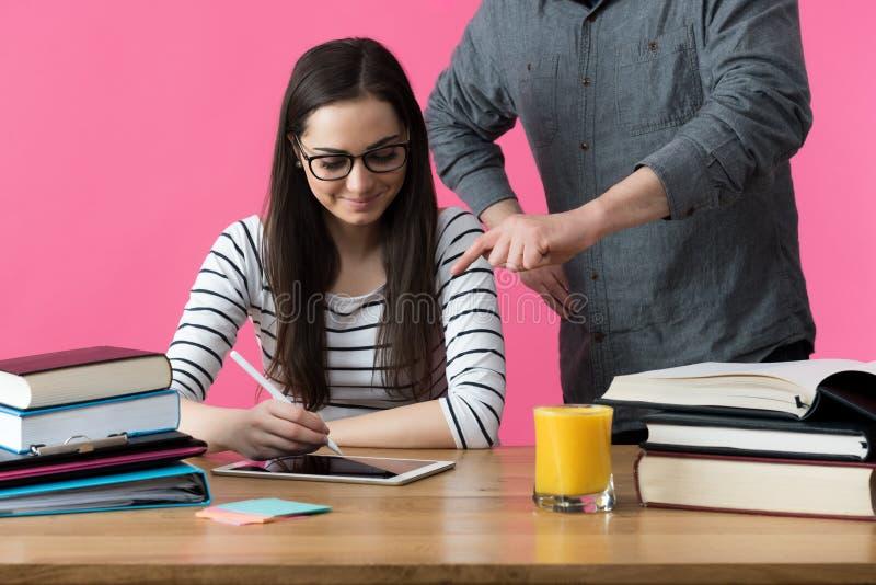 Den kvinnliga studenten som arbetar en till man med handleder Handleda portionstudenten för att förbereda sig för examina royaltyfri foto
