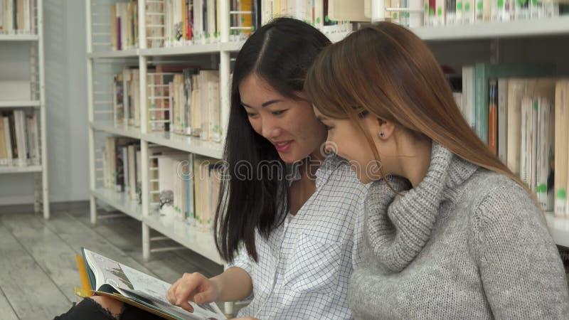 Den kvinnliga studenten visar hennes klasskompis något i boken arkivbilder