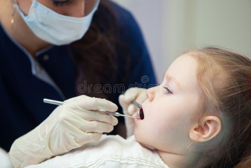 Den kvinnliga tandläkaren i maskering behandlar tandlilla flickan royaltyfria foton