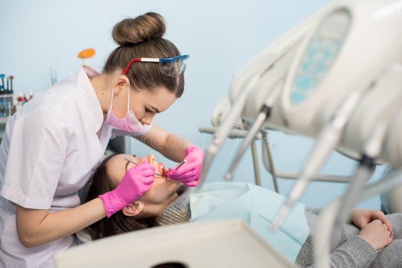 Den kvinnliga tandläkaren med tand- hjälpmedel - avspegla och sondera att kontrollera upp tålmodiga tänder på det tand- klinikkon royaltyfri fotografi