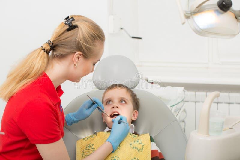 Den kvinnliga tandläkaren undersöker tänderna av det tålmodiga barnet barnmunsned boll som är öppen i stolen för tandläkare` s Nä royaltyfria foton