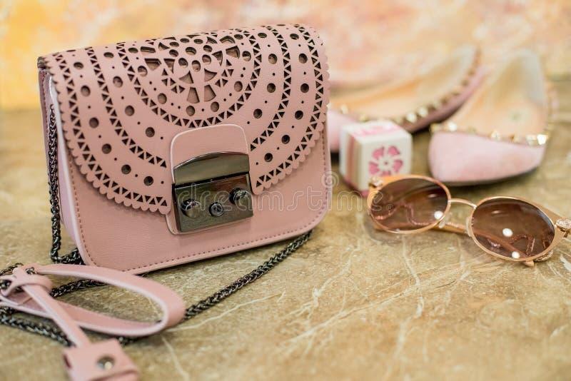 Den kvinnliga tillbehören sänker lekmanna- Kvinnaläderpåse, skor, solexponeringsglas på marmorbakgrund Beiga rosa färgfärgkvinna royaltyfri foto