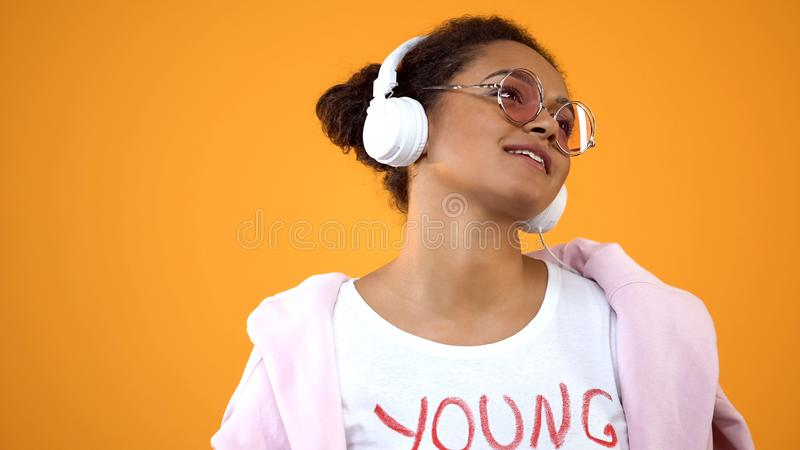 Den kvinnliga tonåringen som lyssnar till musik i vit hörlurar, radiosänder underhållning royaltyfri fotografi