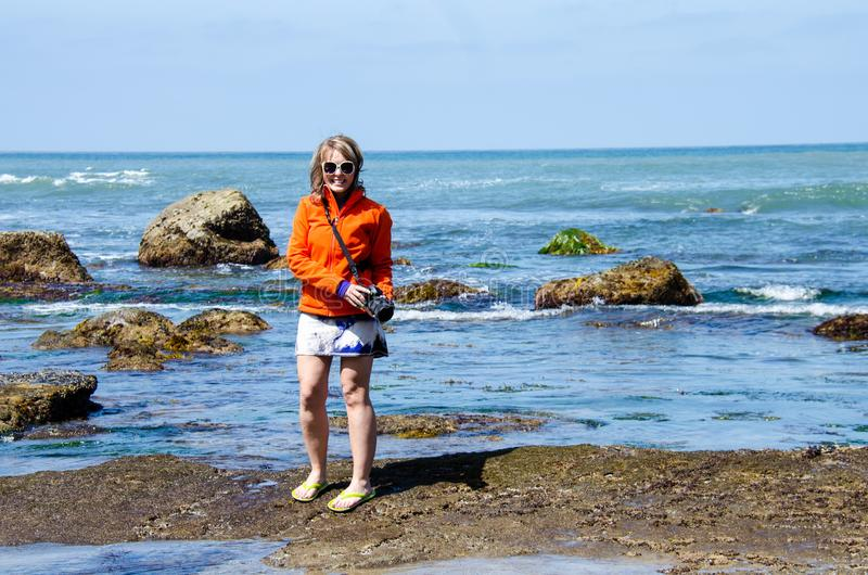 Den kvinnliga turist- fotografen tycker om tipsen för punktCabrillo tidvatten, havsväxt och vaggar i San Diego längs kusterna av  royaltyfri bild