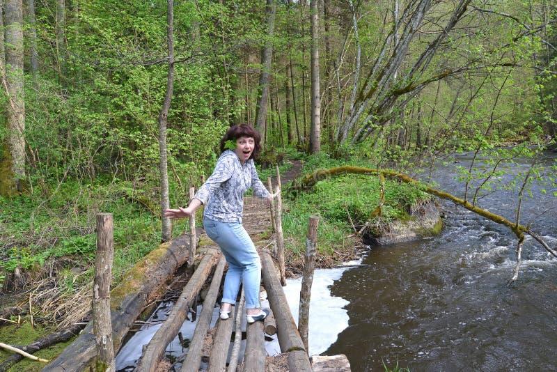 Den kvinnliga turisten med skräck installeras på whroughen den röda floden blå solig russia för tak för daghuskaliningrad region  arkivfoton