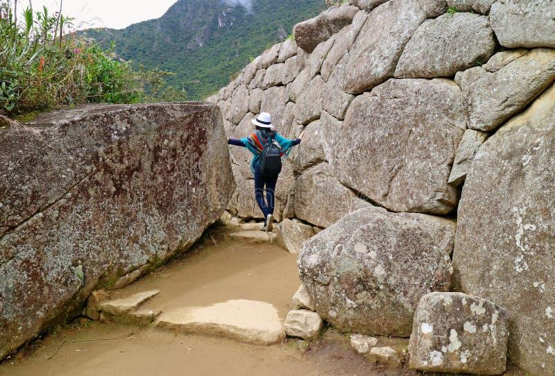 Den kvinnliga turisten som undersöker den forntida incaen, fördärvar av den Machu Picchu citadellen i den Cusco regionen, arkeolo arkivfoton