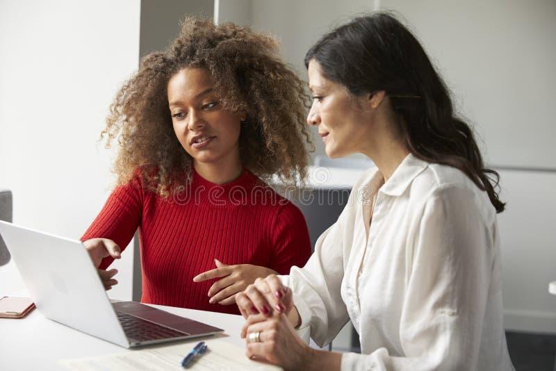 Den kvinnliga universitetsstudenten Working One To en med handleder arkivbilder