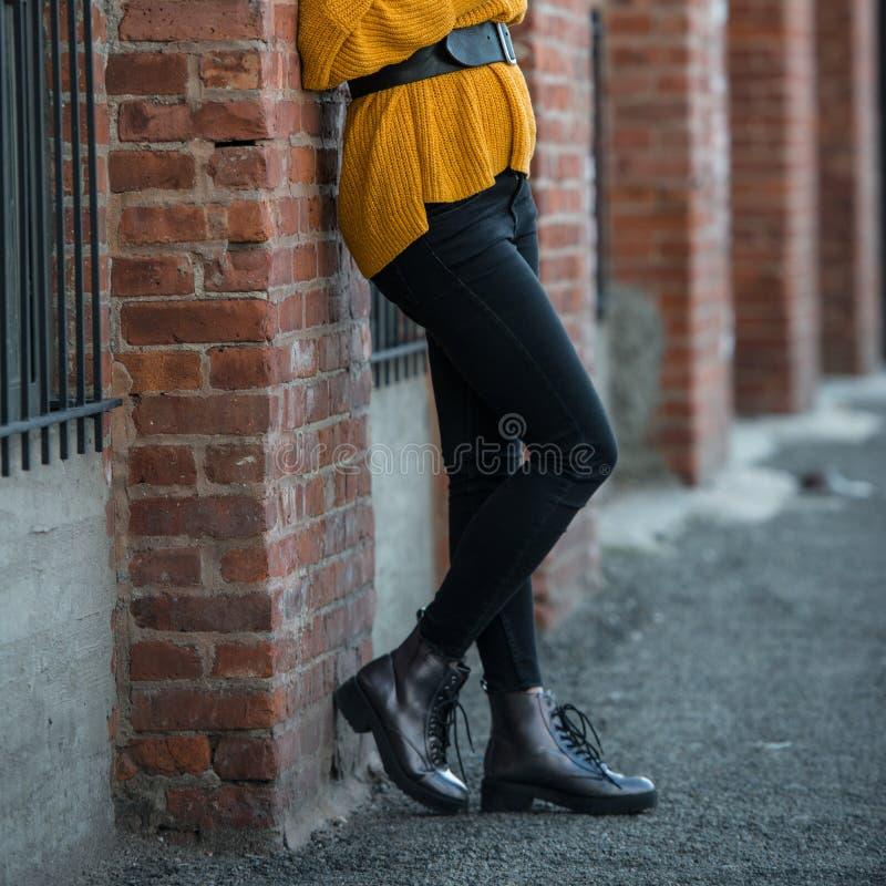 Den kvinnliga vårdräkten med svart mager slank jeans piskar tillfälliga kängor, bältet och den stack tröjan royaltyfria foton