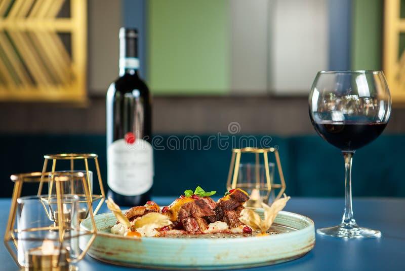 Den läckra bröstanden med mosar potatisen och rött vin på tabellen royaltyfri fotografi