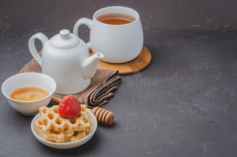 Den läckra frukosten med te, honung och rån dekorerade med den nya jordgubben på en stentabell Copyspace arkivfoton