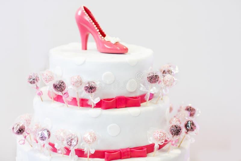 Den läckra härliga bröllopstårtan i vitt och rött med kakan poppar royaltyfri fotografi