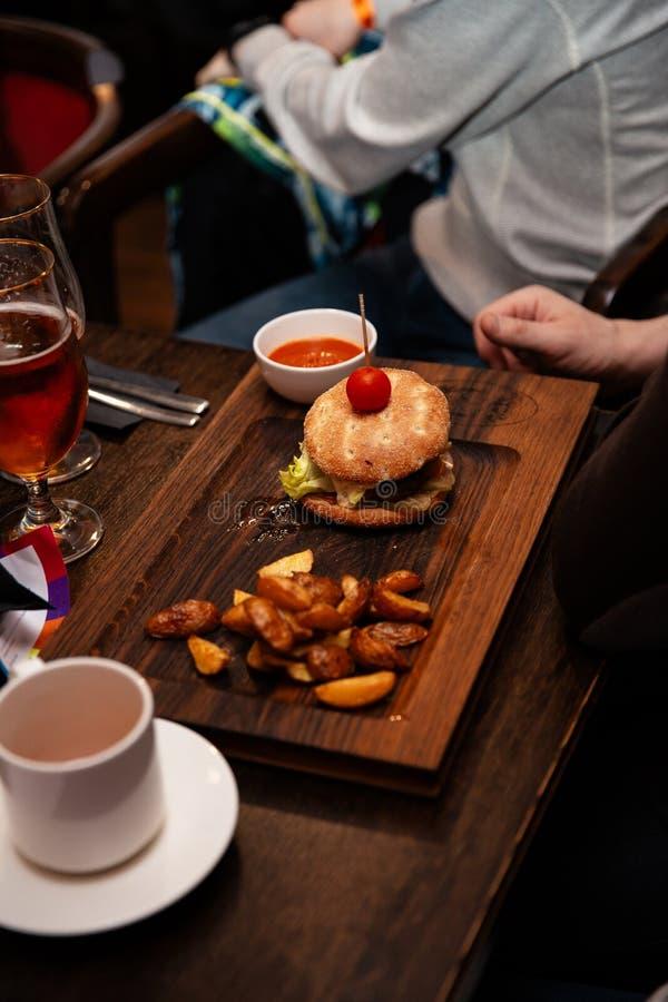 Den läckra hamburgaren med nötköttlilla pastejen, bacon, ost och kål på lantlig träbakgrund tjänade som i en stång arkivfoton