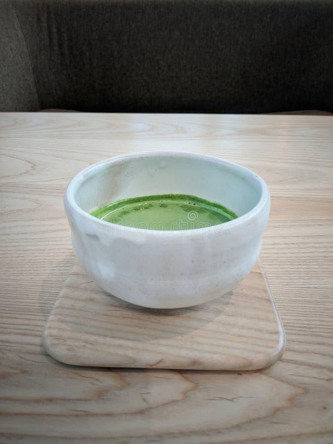 Den läckra matchaen mjölkar te i tekopp för japansk stil arkivbilder
