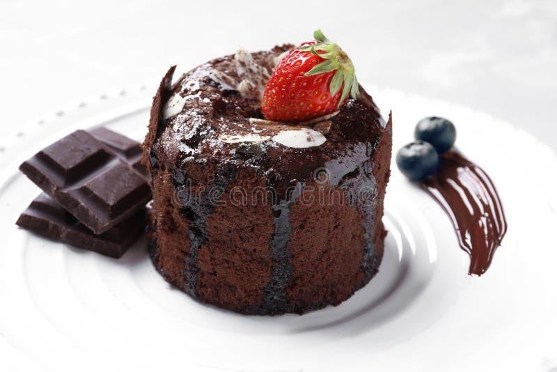 Den läckra nya fondanten med varm choklad och bär tjänade som på plattan Lavakakarecept fotografering för bildbyråer