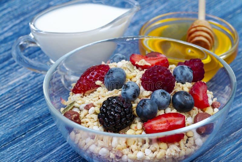 Den läckra sunda myslit med hallonet, blåbäret, jordgubben, Blackberry, hasselnöt, mjölkar och honung på blått trä arkivbild